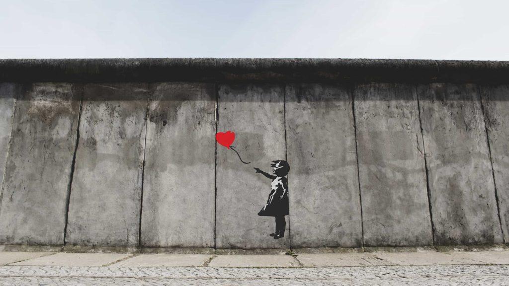 Mural street art of little girl with heart-shaped balloon