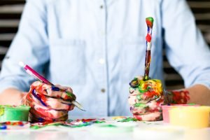 person holding paintbrush, covered in paint