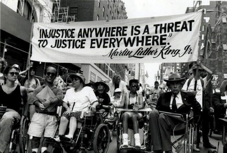 "Black and white photo of a group of people with disabilities at a Disability Rights movement protest. They hold a banner above their heads that says ""Injustice anywhere is a threat to justice everywhere. - Martin Luther King Jr."""
