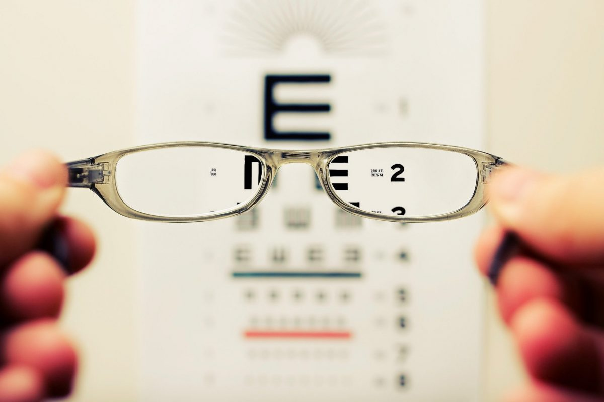 glasses held in front of eye exam chart