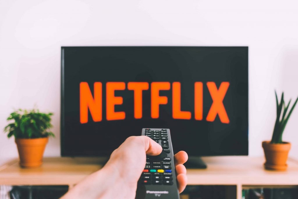 person holding remote and pointing it at a television that has the Netflix logo on display