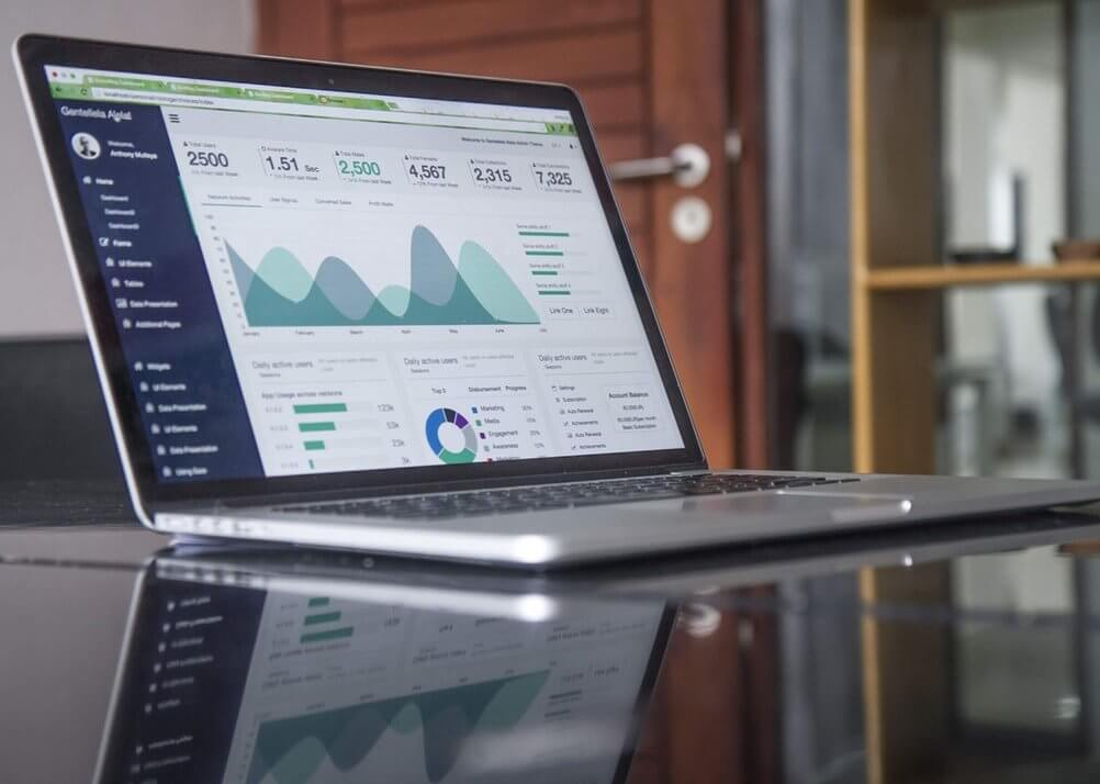 laptop on a table with an analytics dashboard on screen