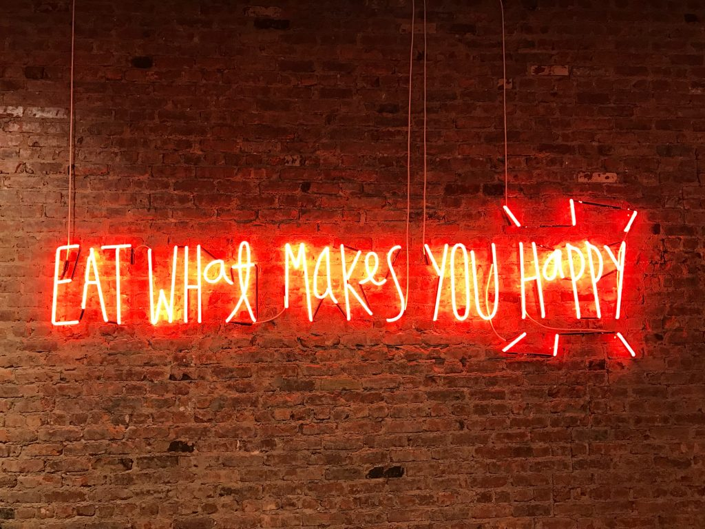 a neon sign that says 'Eat What Makes You Happy