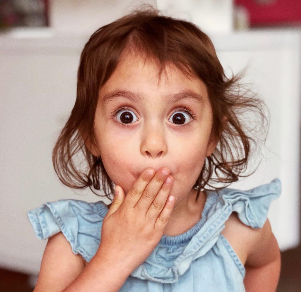 little girl looking surprised covering her mouth