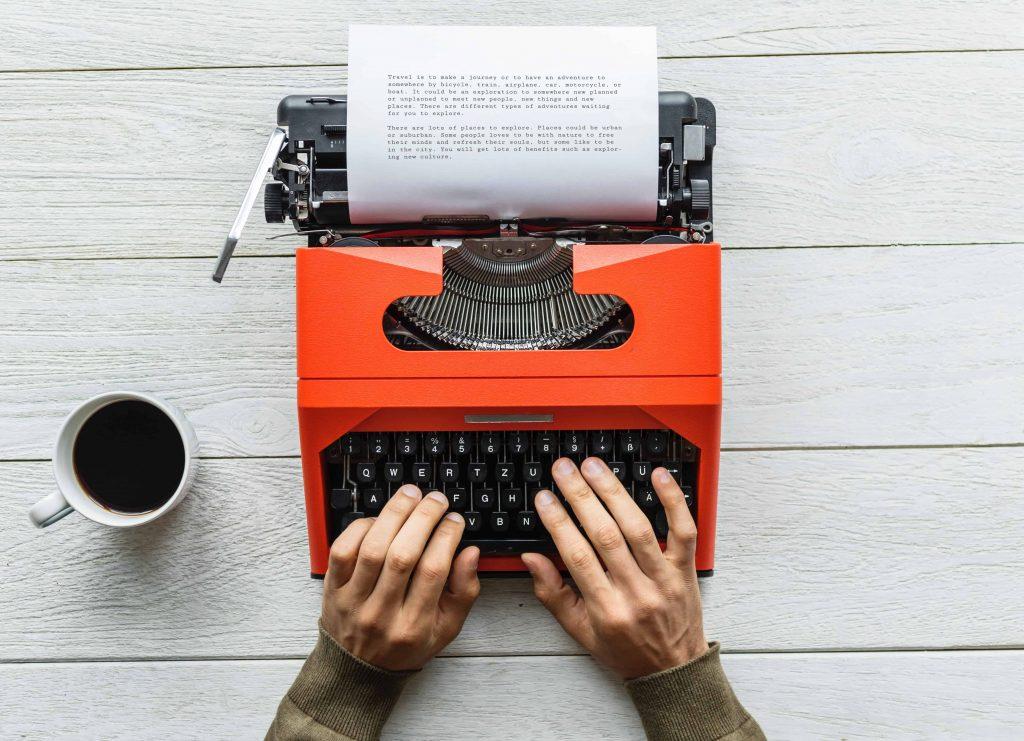 hands typing on a typewriter