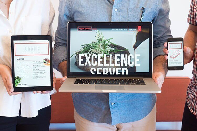 Three people holding a tablet, laptop, and smart phone with jordan steakhouse homepage