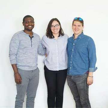 Three team members posing for a photo and smiling