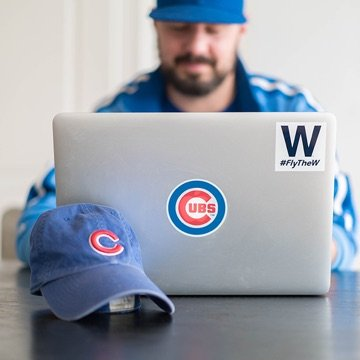 Designer sitting in front of a laptop with a Chicago logo and Chicago Cubs hat