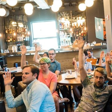 Clique team members raising hands while participating in a workshop