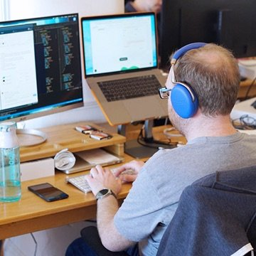 Developer typing on a computer with multiple screens