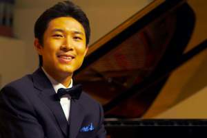 Student in tuxedo smiling in front of piano