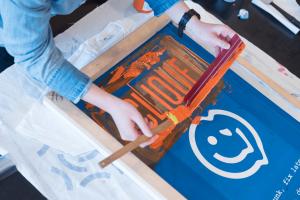 Screen printing the Clique logo onto a shirt with orange paint