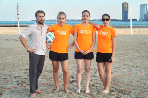 Clique team members posing in matching Clique orange tshirts on a sand volleyball court