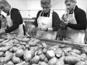 Clique team members wearing aprons and hair nets, packing sweet potatoes