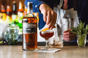 Auchentoshan whisky sitting next to a drink as a hand places an orange rind on top