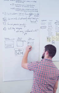 Designer sketching a prototype on a whiteboard