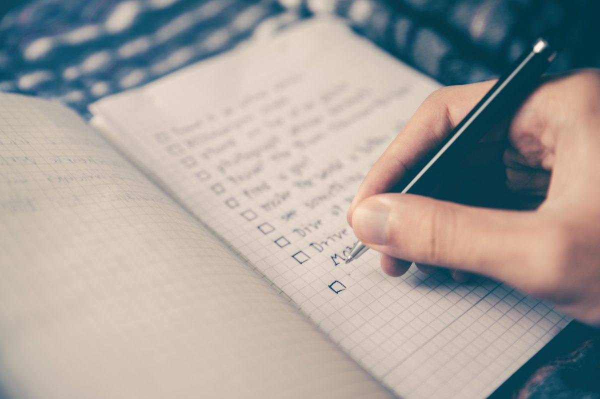 person writing checklist in notebook
