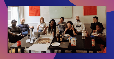 Group photo of Clique employees making silly faces and eating pizza in their office.