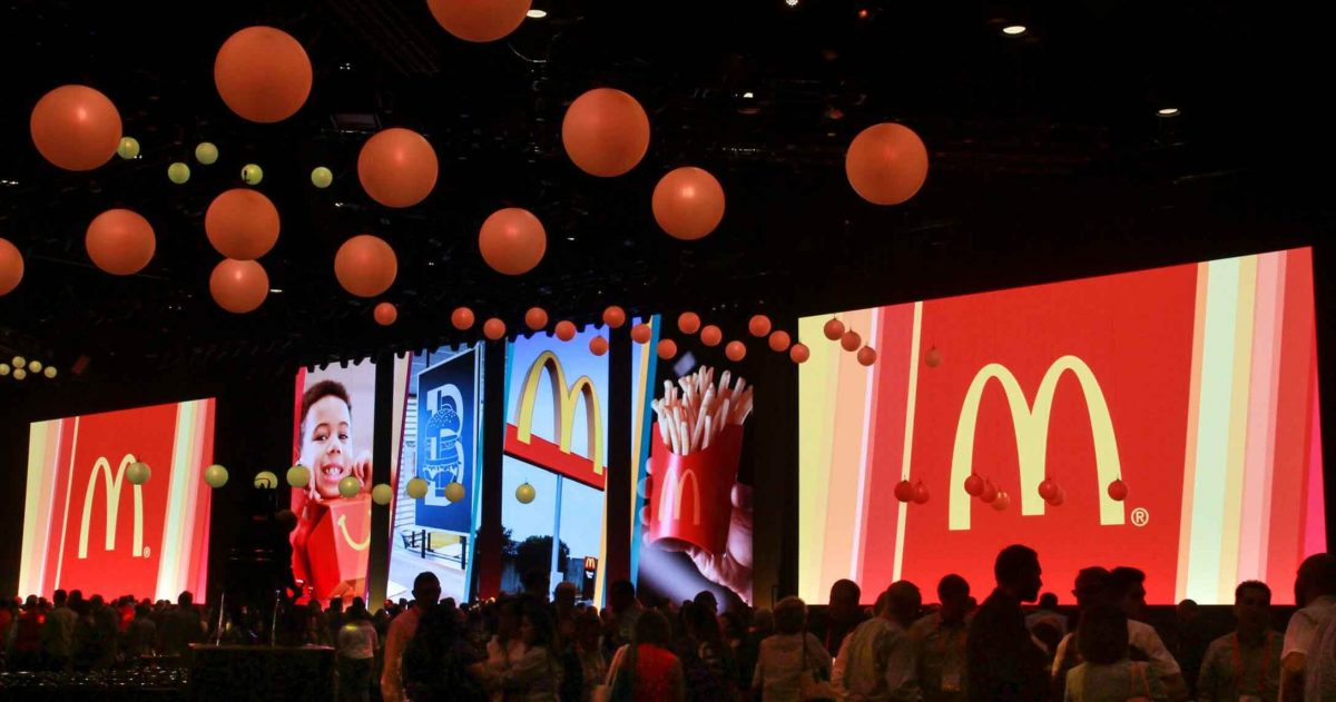 Convention center room for McDonald's event, filled with people