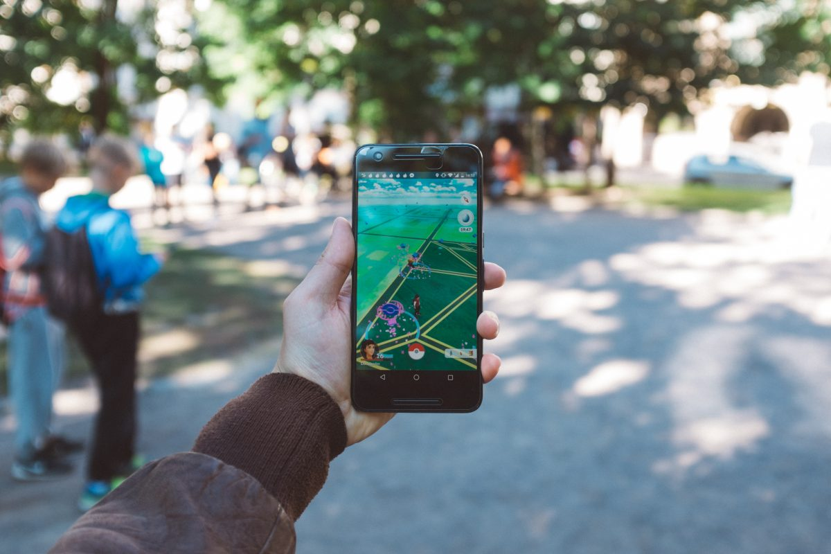Phone held in outstretched hand, screen shows that user is playing Pokémon Go