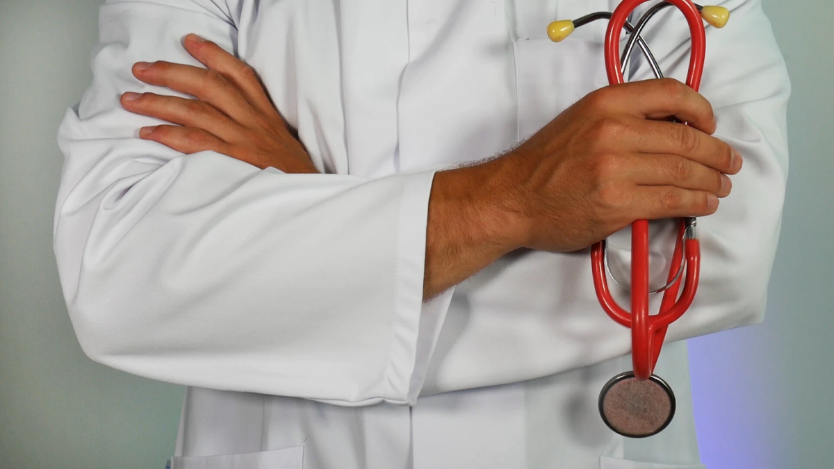A doctor in a lab coat pictured from the waist to the neck with arms crossed, holding a stethoscope