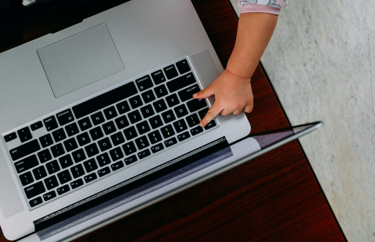 baby hand reaching to type on a computer's keyboard