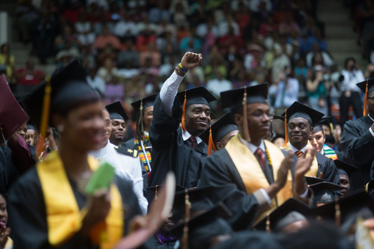 Student in graduation cap and gown lifting is fist in a sea of other graduates