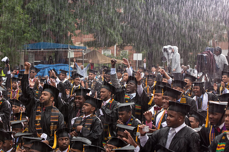 Students in caps and gowns celebrating in the rain